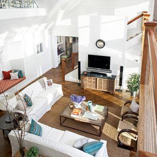 Diseño de salón abierto, costero, grande, con paredes blancas, suelo de madera en tonos medios y televisor colgado en la pared