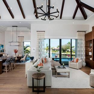 Imagen de salón abierto, tropical, grande, con paredes blancas, pared multimedia, suelo de madera en tonos medios y suelo marrón