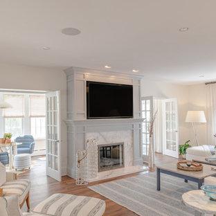 Großes, Abgetrenntes Maritimes Wohnzimmer mit weißer Wandfarbe, Vinylboden, Kamin, Kaminumrandung aus Holz, Multimediawand und braunem Boden in Philadelphia