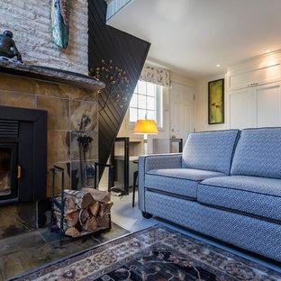 Esempio di un piccolo soggiorno chic stile loft con sala formale, pareti nere, pavimento in legno verniciato, camino classico, cornice del camino in pietra, nessuna TV e pavimento beige