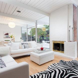 Foto de salón para visitas abierto, vintage, con paredes blancas, suelo de madera clara, chimenea tradicional y marco de chimenea de ladrillo