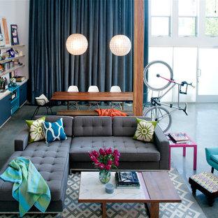 Foto di un soggiorno eclettico con libreria e pavimento in cemento