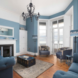 Inspiration for a large nautical open plan living room in Kent with blue walls, medium hardwood flooring, a standard fireplace, a tiled fireplace surround, no tv and brown floors.