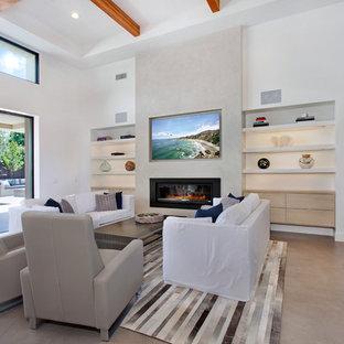 Ispirazione per un soggiorno design di medie dimensioni e aperto con angolo bar, pareti beige, pavimento in cemento, camino classico, cornice del camino in intonaco e parete attrezzata