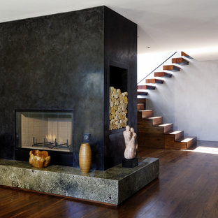 Foto di un soggiorno minimalista di medie dimensioni e chiuso con pareti verdi, pavimento in legno massello medio, camino bifacciale, nessuna TV e cornice del camino in pietra