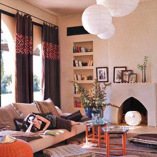 Idée de décoration pour un salon méditerranéen avec un mur beige et une cheminée standard.