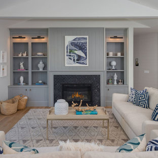 Inspiration for a large beach style open concept and formal medium tone wood floor and brown floor living room remodel in Los Angeles with gray walls, a standard fireplace, a tile fireplace and no tv