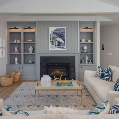 Inspiration for a large coastal open concept and formal medium tone wood floor and brown floor living room remodel in Los Angeles with gray walls, a standard fireplace, a tile fireplace and no tv