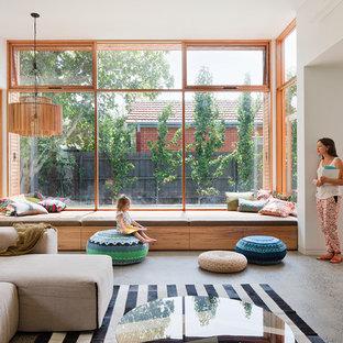 Immagine di un soggiorno contemporaneo di medie dimensioni e aperto con pavimento in cemento e pareti bianche