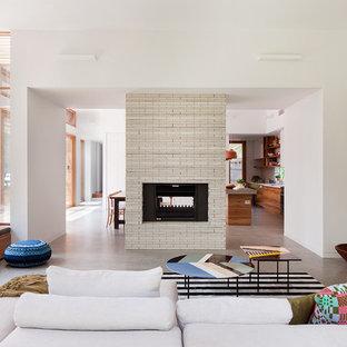 Immagine di un soggiorno contemporaneo di medie dimensioni e aperto con pavimento in cemento, camino bifacciale, cornice del camino piastrellata e pareti bianche