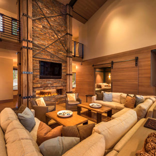 Imagen de salón abierto, abovedado y madera, rústico, extra grande, madera, con paredes beige, suelo de madera en tonos medios, chimenea lineal, marco de chimenea de piedra, televisor colgado en la pared, suelo marrón y madera
