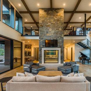 На фото: большая открытая гостиная комната в современном стиле с белыми стенами, светлым паркетным полом, двусторонним камином, фасадом камина из бетона, телевизором на стене, коричневым полом и музыкальной комнатой с