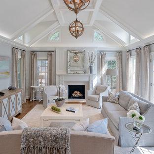 Idee per un grande soggiorno tradizionale aperto con pavimento in legno massello medio, camino classico, cornice del camino in pietra, TV nascosta, pavimento marrone e pareti grigie