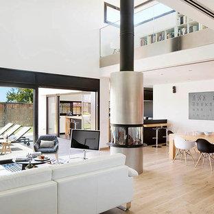 Diseño de salón para visitas abierto, moderno, grande, con paredes blancas, suelo de madera clara, chimeneas suspendidas y televisor independiente