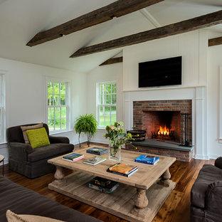Inspiration för lantliga vardagsrum, med vita väggar, mellanmörkt trägolv, en standard öppen spis, en spiselkrans i tegelsten och en väggmonterad TV