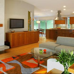 Diseño de salón abierto, minimalista, grande, con suelo de bambú, paredes multicolor, marco de chimenea de hormigón, televisor colgado en la pared y suelo marrón