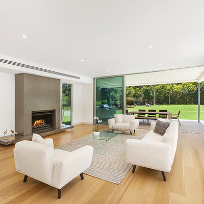 Example of a large minimalist open concept and formal light wood floor living room design in Central Coast with a standard fireplace and white walls