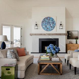 ニューヨークの大きいビーチスタイルのおしゃれなLDK (白い壁、無垢フローリング、標準型暖炉、石材の暖炉まわり、テレビなし、青い床) の写真