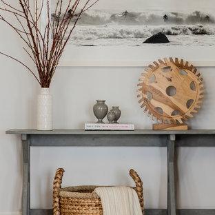 Imagen de salón abierto, costero, grande, sin televisor, con paredes blancas, suelo de madera en tonos medios, chimenea tradicional, marco de chimenea de piedra y suelo azul