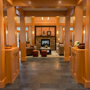 Foto di un grande soggiorno tradizionale aperto con sala formale, pareti grigie, nessuna TV, camino classico, cornice del camino in pietra, pavimento in gres porcellanato e pavimento nero