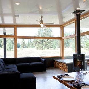 Esempio di un piccolo soggiorno design aperto con pareti nere, pavimento in cemento, stufa a legna e nessuna TV
