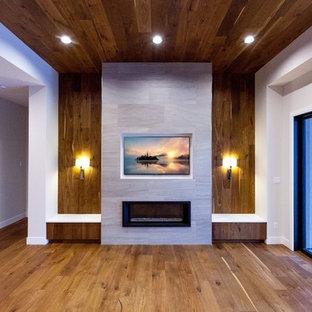 Imagen de salón abierto, minimalista, grande, con paredes grises, suelo de madera en tonos medios, chimeneas suspendidas, marco de chimenea de baldosas y/o azulejos, televisor colgado en la pared y suelo marrón