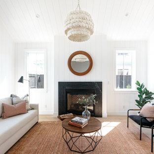 ロサンゼルスの中くらいのカントリー風おしゃれなLDK (白い壁、標準型暖炉、石材の暖炉まわり、無垢フローリング、茶色い床、塗装板張りの天井、三角天井、塗装板張りの壁) の写真