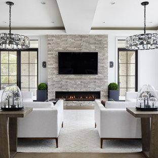ワシントンD.C.の大きい地中海スタイルのおしゃれなLDK (白い壁、淡色無垢フローリング、壁掛け型テレビ、ベージュの床) の写真