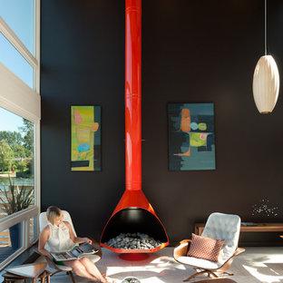 シアトルのミッドセンチュリースタイルのおしゃれなリビング (黒い壁、吊り下げ式暖炉) の写真