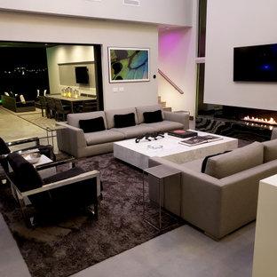 ラスベガスの広いモダンスタイルのおしゃれなLDK (グレーの壁、コンクリートの床、横長型暖炉、石材の暖炉まわり、壁掛け型テレビ、グレーの床、折り上げ天井) の写真