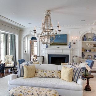 Modelo de salón para visitas clásico, grande, sin televisor, con paredes blancas, suelo de madera oscura, chimenea tradicional, marco de chimenea de madera y suelo marrón