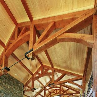 他の地域の大きいおしゃれなリビングロフト (茶色い壁、無垢フローリング、標準型暖炉、石材の暖炉まわり、内蔵型テレビ) の写真