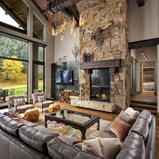 Modelo de salón abierto, rural, grande, con paredes blancas, suelo de madera en tonos medios, chimenea tradicional, marco de chimenea de piedra, televisor colgado en la pared y suelo marrón
