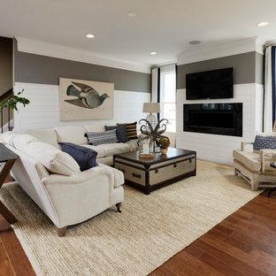 ワシントンD.C.の巨大なビーチスタイルのおしゃれなLDK (フォーマル、マルチカラーの壁、クッションフロア、壁掛け型テレビ、茶色い床、横長型暖炉、木材の暖炉まわり) の写真
