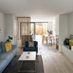 Diseño de salón abierto, moderno, con suelo de madera clara, estufa de leña y marco de chimenea de yeso