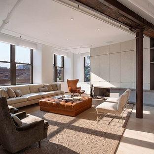 Imagen de salón moderno con marco de chimenea de hormigón y televisor retractable