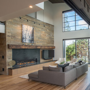 Large contemporary open plan living room in Seattle with white walls, medium hardwood flooring, a ribbon fireplace, a wall mounted tv, brown floors, a metal fireplace surround and feature lighting.