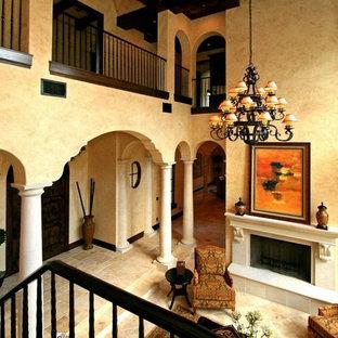 オーランドの広い地中海スタイルのおしゃれなリビングロフト (ベージュの壁、トラバーチンの床、標準型暖炉、石材の暖炉まわり、テレビなし、ベージュの床) の写真