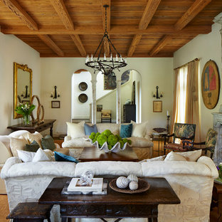 Medelhavsstil inredning av ett vardagsrum, med ett finrum, vita väggar, mellanmörkt trägolv, en standard öppen spis och en spiselkrans i sten