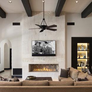フェニックスの地中海スタイルのおしゃれなリビング (白い壁、横長型暖炉、タイルの暖炉まわり、壁掛け型テレビ、ベージュの床) の写真