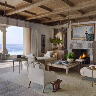 オレンジカウンティの中くらいの地中海スタイルのおしゃれなLDK (フォーマル、白い壁、標準型暖炉、淡色無垢フローリング、石材の暖炉まわり、テレビなし、ベージュの床) の写真