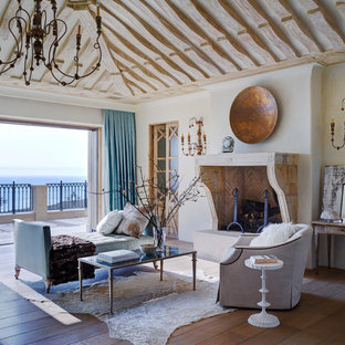 Inspiration for a huge mediterranean medium tone wood floor and brown floor living room remodel in Orange County with white walls, a standard fireplace and a stone fireplace