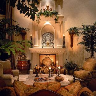 Ispirazione per un soggiorno mediterraneo di medie dimensioni e chiuso con pareti beige, camino classico, nessuna TV, sala formale, pavimento in travertino, cornice del camino in intonaco e pavimento beige