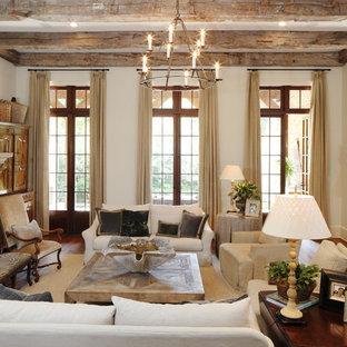 Cette photo montre un salon méditerranéen fermé avec une salle de réception, un mur beige, un sol en bois brun, une cheminée standard et un manteau de cheminée en pierre.