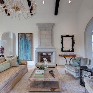 Immagine di un ampio soggiorno mediterraneo aperto con sala formale, pareti bianche, pavimento in pietra calcarea, camino classico, cornice del camino in pietra e nessuna TV