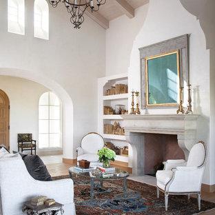 Mediterranes Wohnzimmer mit weißer Wandfarbe, braunem Holzboden und Kamin in Austin