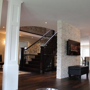 トロントの中サイズの地中海スタイルのおしゃれなLDK (ベージュの壁、濃色無垢フローリング、横長型暖炉、石材の暖炉まわり、テレビなし) の写真