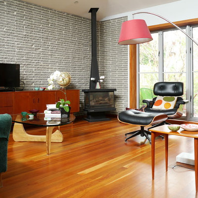 1960s medium tone wood floor living room photo in Melbourne with white walls, a wood stove and a tv stand