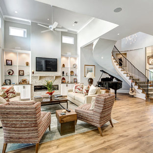 Example of a transitional medium tone wood floor and brown floor living room design in Houston with gray walls, a ribbon fireplace and a stone fireplace