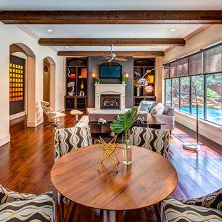 Modelo de salón abierto, tradicional renovado, grande, con suelo de madera en tonos medios, chimenea tradicional, televisor colgado en la pared y paredes beige